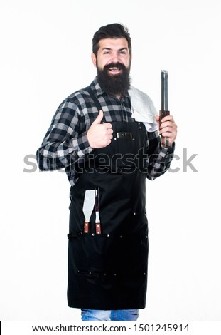 Picnic and barbecue. Cooking meat in park. Barbecue master. Bearded hipster wear apron for barbecue. Roasting and grilling food. Man hold cooking utensils barbecue. Tools for roasting meat outdoors.