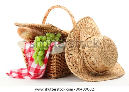 Picnic basket and straw hat isolated on white background