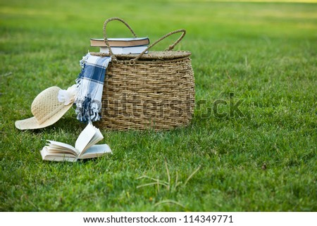 Picnic basket and straw hay laying on the grass. Also available in vertical format.