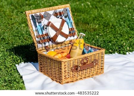 Picnic Basket Food On White Blanket In Summer