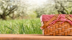 Picnic basket on a table against the background of nature. Rest and summer mood. Departure for a picnic on the weekend or vacation.