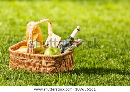 picnic basket on green lawn - stock photo