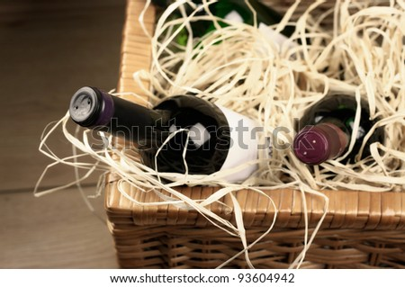 Picnic basket with bottles of red and white wine in straw.