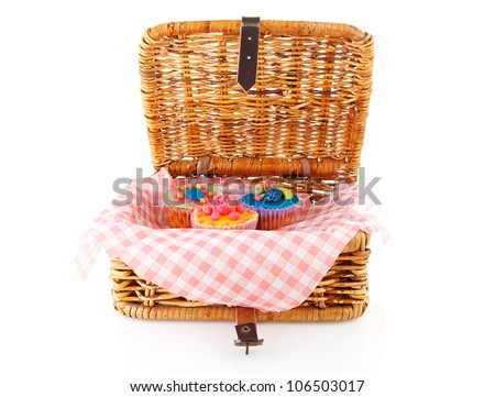 Picnic basket with decorated cupcakes over white background