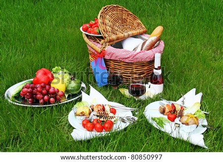 Picnic basket with different food on grass