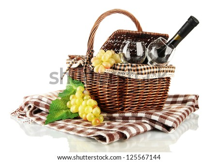 Picnic basket with fruits and bottle of wine isolated on white