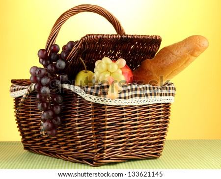 Picnic basket with fruits on cloth on yellow background