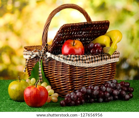 Picnic basket with fruits on grass on bright background