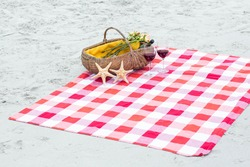 Picnic basket with glasses of red wine and starfishes on a blanket at the beach