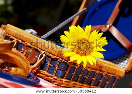 picnic basket with sunflower and sweet dessert on the table