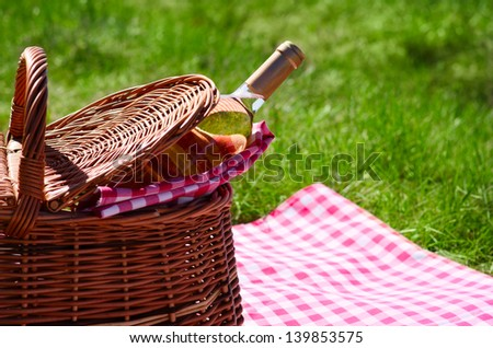 Picnic basket with wine bottle at lawn
