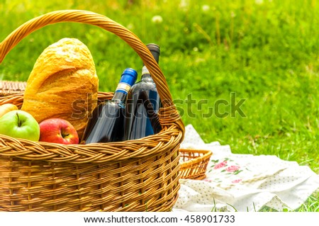Picnic basket with wine, fruits and bread on a sunny, green and grassy background