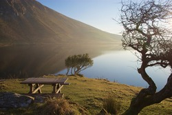 Picnic bench in early morning scene at Annascaul Lake, a popular tourist attraction in Co. Kerry, Ireland.