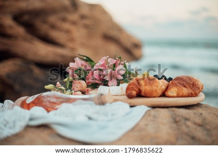 Picnic by the sea. Close-up flowers, croissants and a bottle of wine. Side view. Stockfoto ©