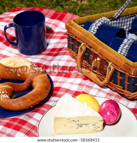 picnic cloth with basket and food on it