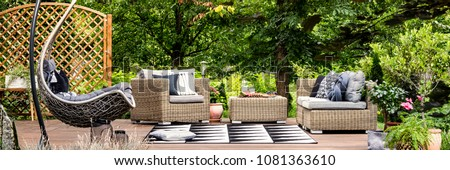 Picnic food and cold lemonade in glass carafe placed on a garden table standing on a terrace with hammock chair