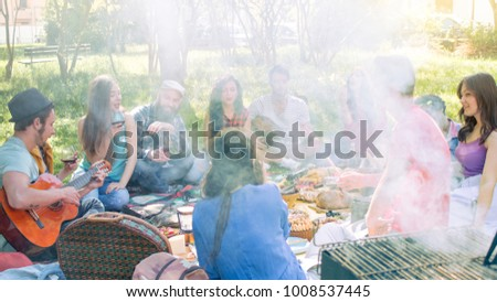 picnic friends having fun and smoking barbecue grill. group of friends sitting eating and drinking in a park on a sunny day