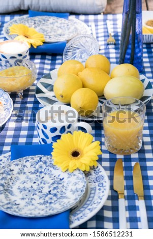 Picnic in nature. Elegant table setting in blue, gold cutlery, ceramic plates, checkered tablecloth, a dessert of waffles, lemonade and fruit, cup of coffee. Yellow marigold flowers in vase. Top view. Foto stock ©