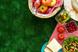 picnic in summer with products, sandwich, salad, fruits, drink and hat on green grass texture background top view mockup