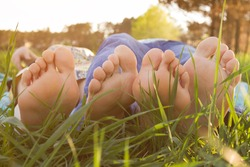 picnic, male and female feet on the green grass