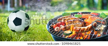 Picnic on a meadow with bratwurst on flaming grill and a soccer ball