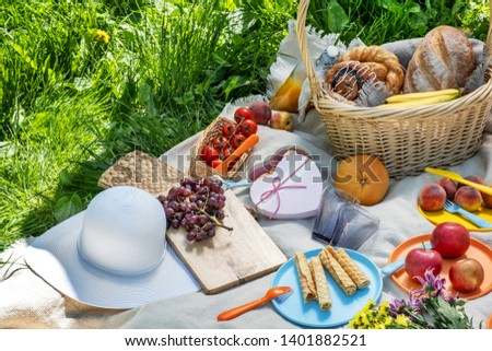 picnic on green grass. Basket with bread and a bottle and bananas in a basket and tomatoes with apples. still life on green grass. blanket and food for a picnic in summer Park