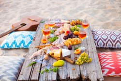 Picnic on the beach at sunset in the style of boho, food and drink conception