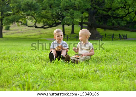 Picnic on the grass. Two little boys have a dinner with pizza on the meadow at the noon