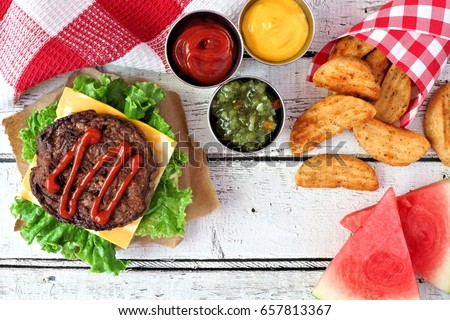 Picnic scene with open hamburger, watermelon and potato wedges on white wood background