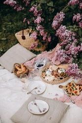 picnic setting for two. white blanket for picnic outdoors. cheese plate, pastries and picnic snacks. two transparent glasses with wine. picnic in the garden.