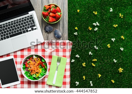 Picnic setting on a outdoor table with fresh salad bowl, laptop and tablet