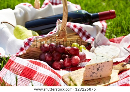 Picnic setting with wine, blue cheese, pears and grapes
