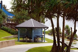 Picnic shade structure beside a beachfront walking track in landscaped gardens