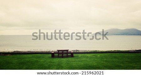 Picnic Table Benches and seascape in Waterville, County Kerry - vintage effect. Outdoor Table along the Ring of Kerry - retro photo. Panoramic coastal photo. Ireland. Wide photo for web page slider.