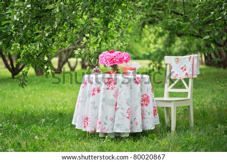 Picnic table with beautiful bouquet of pink peony on it and chair in beautiful park