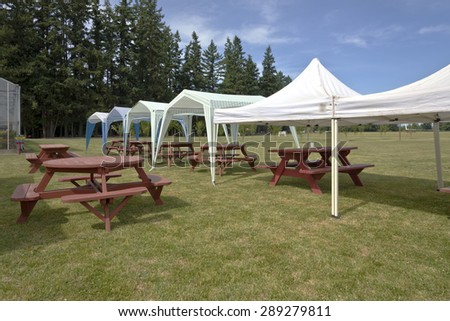 Picnic tables and tent gazebos on an outdoor lawn Canby Oregon.