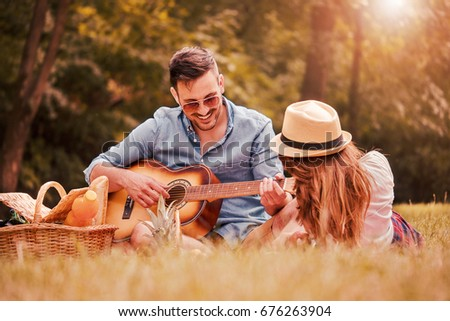 Picnic time. Young couple having fun with guitar on picnic in the park. Love and tenderness, dating, romance, lifestyle concept