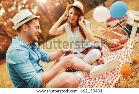 Picnic time. Young couple listening to music during picnic in the park, having fun together. Love and tenderness, dating, romance, lifestyle concept