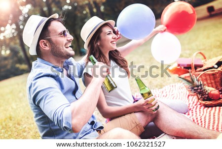 Picnic time. Young smiling couple drinking beer and enjoying in picnic day. Love and tenderness, dating, romance, lifestyle concept