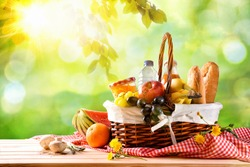Picnic wicker basket with food on table in the field with green nature background. Picnic concept. Front view. Horizontal composition.