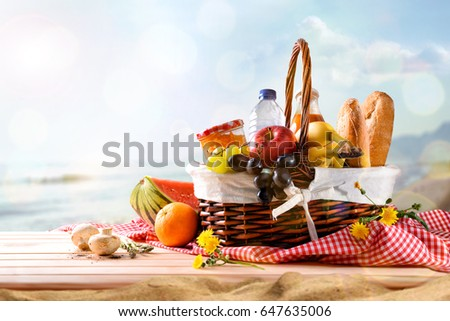 Picnic wicker basket with food on wood table on the beach with blue sky background and sun. Picnic concept. Front view. Horizontal composition.