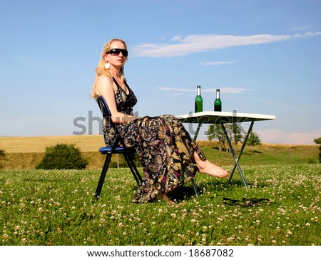 Picnic with a young and beautiful woman with a nice sundress sitting awaiting and enjoying at a table with two beer bottles in front of a beautiful natural landscape.