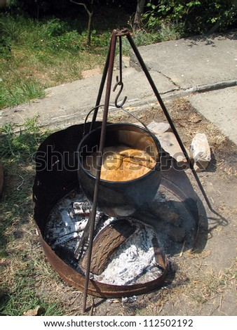 Picnic with traditional organic camp stew made on camping fire in old pot