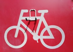Pictogram with a white bicycle on a red background in the parking lot and with a bicycle lifting structure.