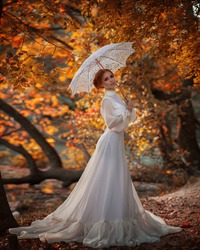 Pictorial landscape amazing cute young woman in fairy-tale image with fire red hair in white long dress holds white lace umbrella in her hands and stands in bright yellow autumn forest with trees