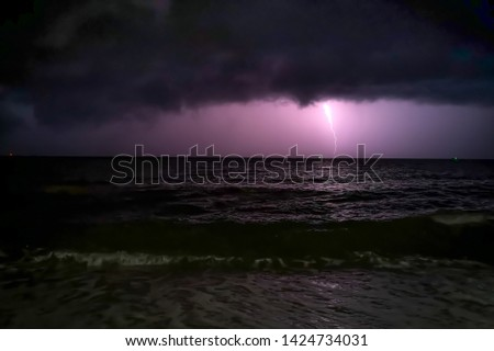 Picture at nigh of sea with waves. There is lightning down and can see dense clouds on sky.