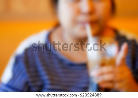Picture blurred abstract background of fat woman drink cola
