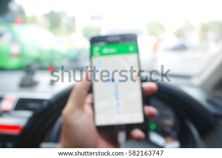 Picture blurred  for background abstract and can be illustration to article of Hand using a smartphone while driving a car #582163747