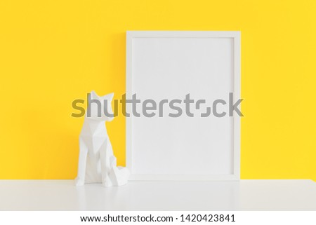 Picture frame and origami fox object decor near yellow wall. Mockup