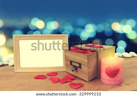 picture frame and red hearts are pouring from wooden box  on blur bokeh light in city in blue tone background